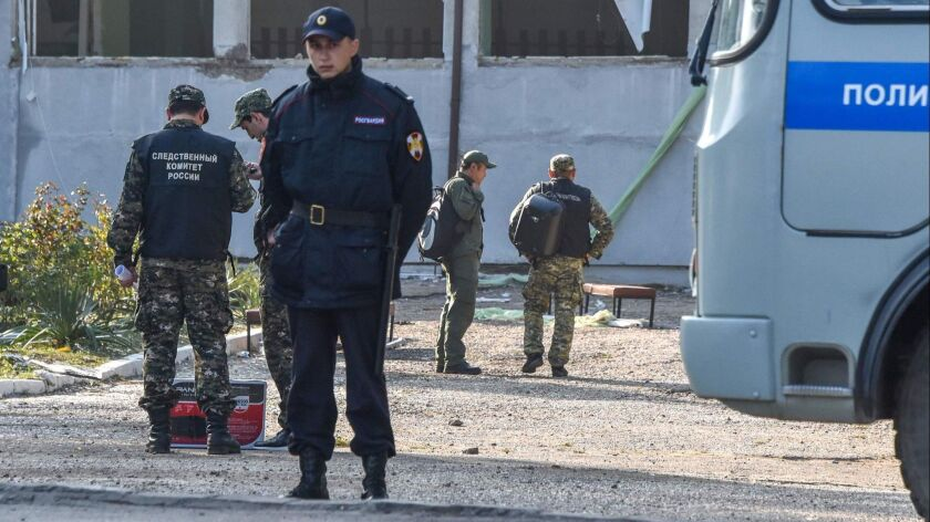 Members of Russia's Investigative Committee work at a college in Kerch, Crimea, on Oct. 18 after a student opened fire.