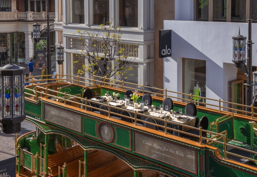 A long table with place settings sits on the top deck of a trolley.