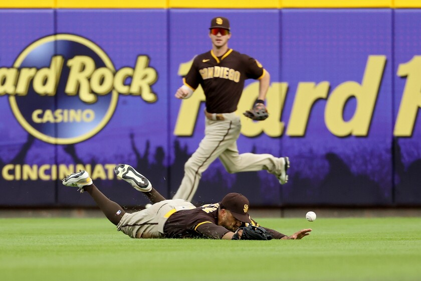 Padres' Trent Grisham dives in attempt to catch a fly ball in the second inning as Wil Myers closes in.