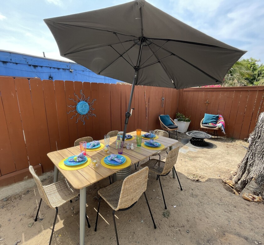 The Ibarras' backyard has a patio dining set with umbrella and chairs around a fire pit.