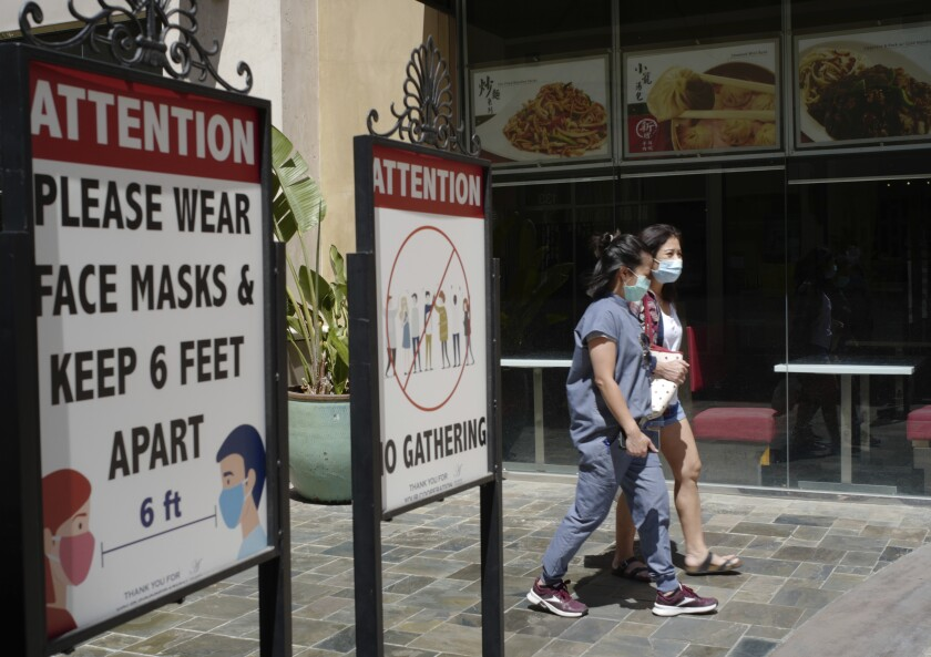 File - In this June 11, 2021 file photo customers wear face masks in an outdoor mall with closed business amid the COVID-19 pandemic in Los Angeles. Coronavirus cases have jumped 500% in Los Angeles County over the past month and health officials warned Tuesday, July 13, 2021, that the especially contagious delta variant of the disease continues to spread rapidly among California's unvaccinated population. (AP Photo/Damian Dovarganes,File)
