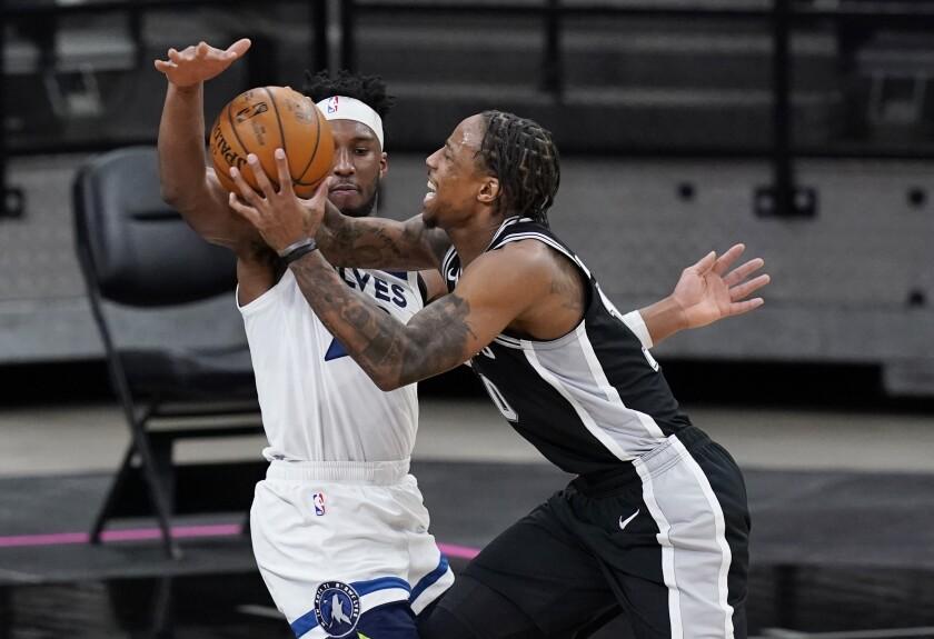 San Antonio Spurs forward DeMar DeRozan, right, drives against Minnesota Timberwolves guard Josh Okogie during the second half of an NBA basketball game in San Antonio, Wednesday, Feb. 3, 2021. (AP Photo/Eric Gay)