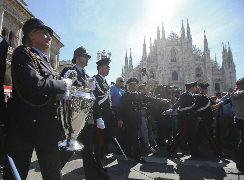 Local police officers hold the Champions League trophy in front of the Duomo gothic cathedral, during the unveiling of the Champions Festival event, in Milan, Italy, Thursday, May 26, 2016. The Champions League soccer final between Real Madrid and Atletico Madrid will be held at the San Siro stadiu