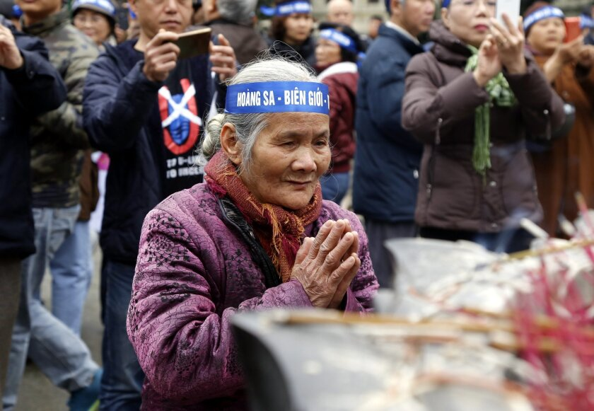A Vietnamese woman prays as more than 100 Vietnamese people gather in central Hanoi Wednesday, Feb. 17, 2016 to commemorate the anniversary of the start of Vietnam's brief but bloody border war with China. The residents lit incense and laid flowers at the statue of King Ly Thai To, a Vietnamese her