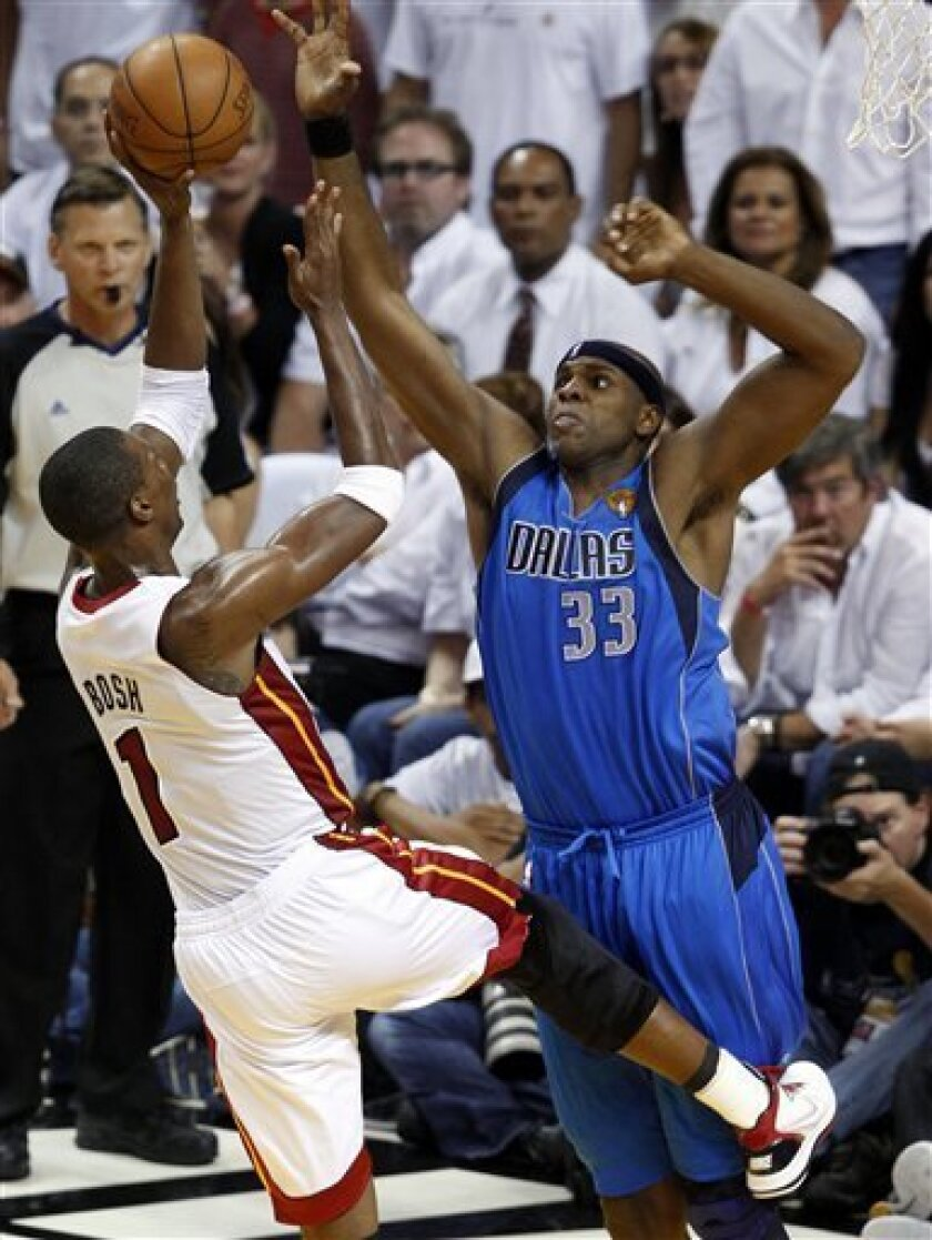 Dallas Mavericks' Brendan Haywood (33) attempts to block a shot by Miami Heat's Chris Bosh (1) during the second half of Game 1 of the NBA Finals basketball game Tuesday, May 31, 2011, in Miami. (AP Photo/Wilfredo Lee)