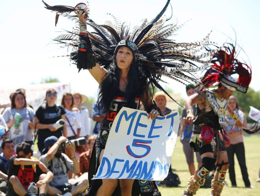 Yolanda Santoya from the Los Angeles dance group La Cuauhtemoc performs the opening ceremony before a large group marches to Corcoran State Prison in support of prison inmates holding a statewide hunger strike.