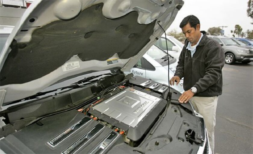 Prem Menon of General Motors checked the hydrogen-fuel-cell engine  compartment of a modified Chevrolet Equinox, one of 11 vehicles from seven manufacturers participating in the tour. (Howard Lipin / Union-Tribune)