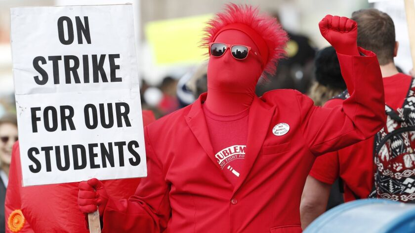 An teacher holds a placard during a march to Denver Public Schools headquarters to deliver Valentine's Day cards Wednesday.