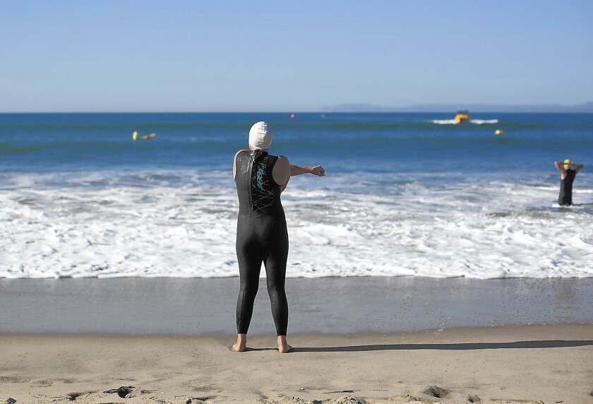 A prospective lifeguard stretches before a tryout in March at Huntington State Beach. A stretch of the beach at Brookhurst Street was ranked the 10th most polluted in California by environmental group Heal the Bay in its latest Beach Report Card.