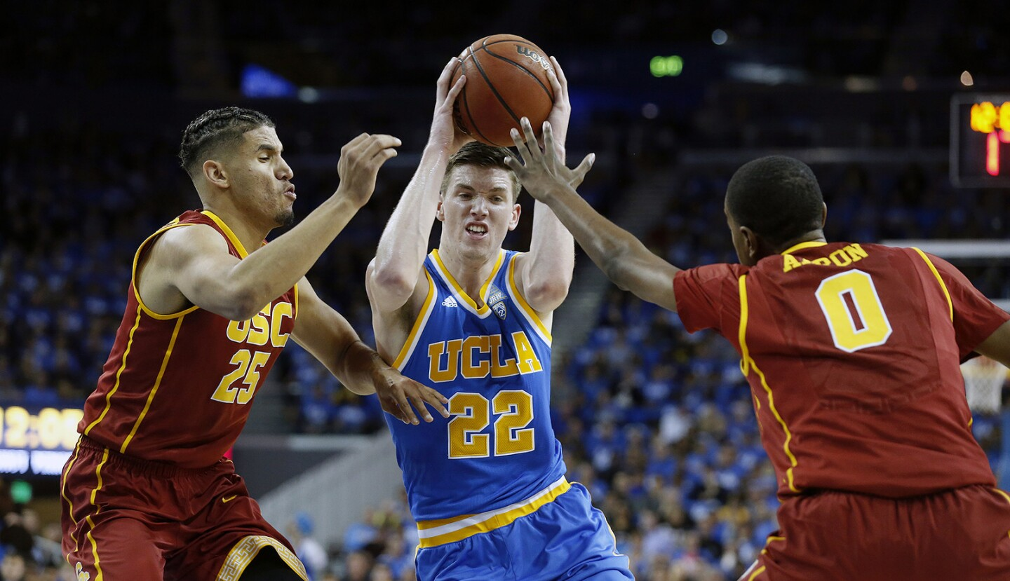 UCLA forward TJ Leaf (22) drives to the basket guarded by USC forward Bennie Boatwright (25) and guard Shaqquan Aaron in the first half of the Bruins' 102-70 win at Pauley Pavilion on Feb.18.