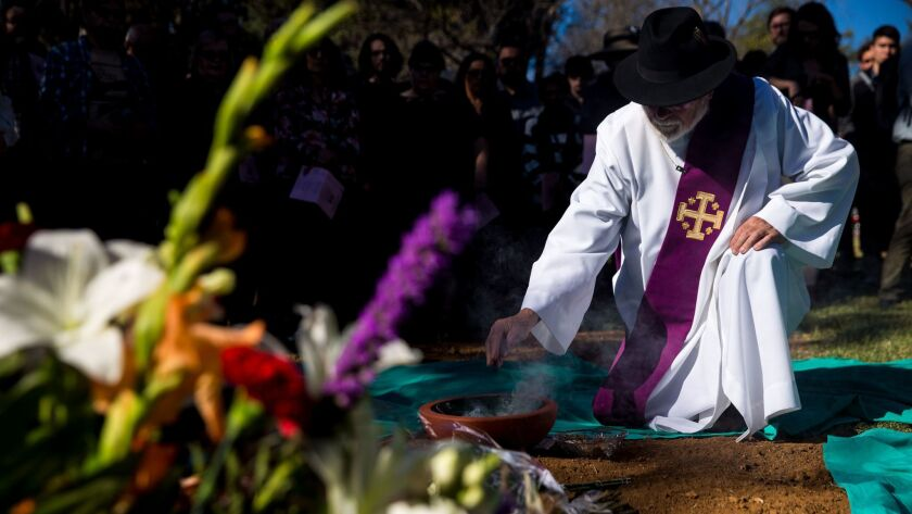 LOS ANGELES, CA - DECEMBER 06: A clergyman kneels down to pay their respects during an interfaith se