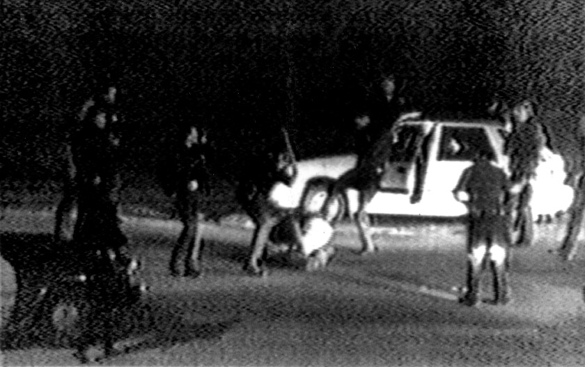 Black-and-white video footage of LAPD officers beating Rodney King