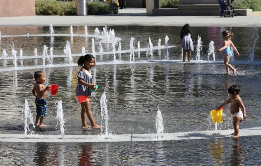 Niños juegan en una fuente durante un día caluroso en el centro de Los Ángeles (EE.UU.). EFE/Archivo