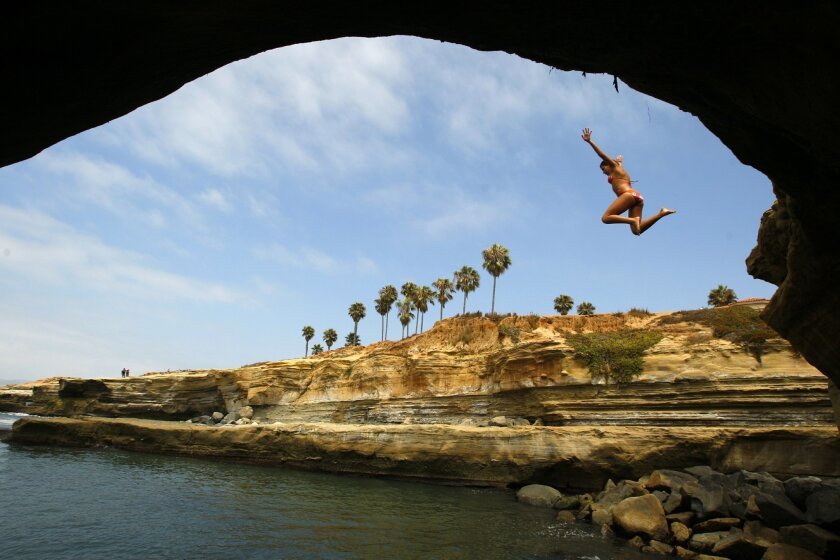 Despite signs saying cliff jumping is prohibited at Sunset Cliffs Natural Park, Ellie Stone, 19, of La Mesa leapt into the cool waters below. (K.C. Alfred / Union-Tribune)