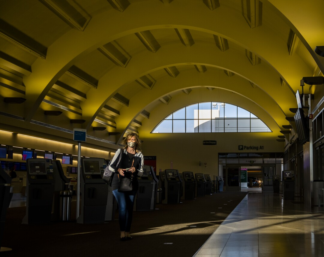 A traveler wearing a mask makes her way through John Wayne Airport in Orange County.