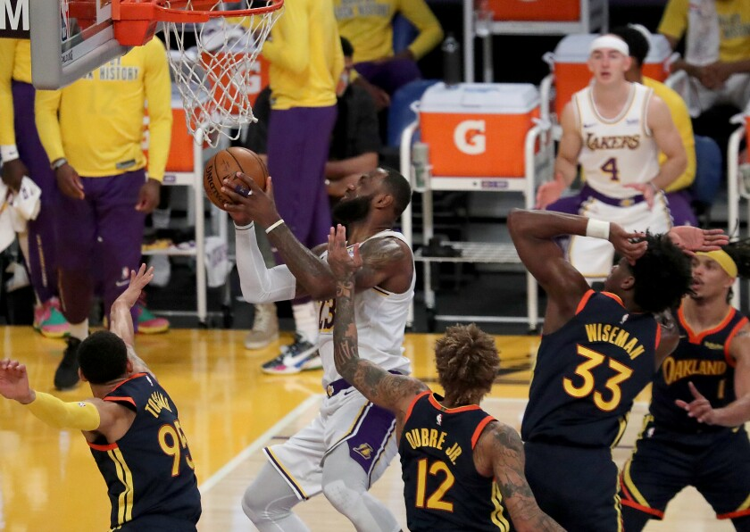 Lakers star LeBron James, center, is fouled by Golden State's Kelly Oubre Jr. while driving to the basket.