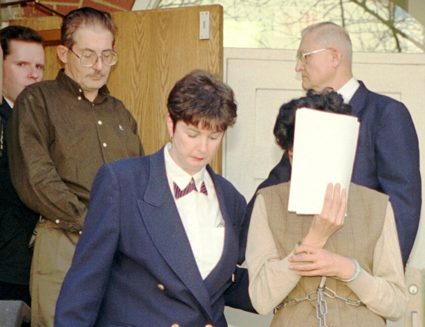 Maria del Rosario Casas Ames, with face covered, and her husband, Aldrich Ames, upper left, leave a federal courthouse in 1994. He is serving a life sentence for espionage. She was sentenced to five years in prison for conspiring to commit espionage and tax evasion.
