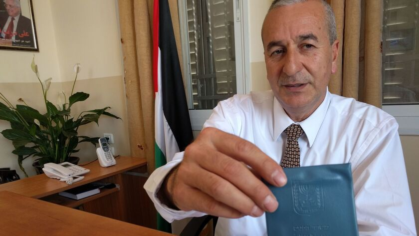 Imad Awad, the head of the Palestinian Authority-run local council for Kafr Aqab shows his Israel ID