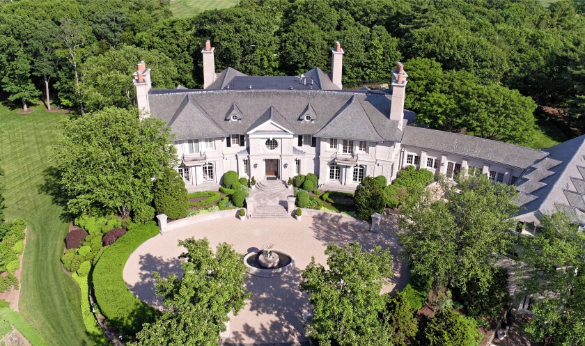Set on seven acres, the 27,000-square-foot mansion is surrounded by lush landscaping, rolling lawns and meandering paths.