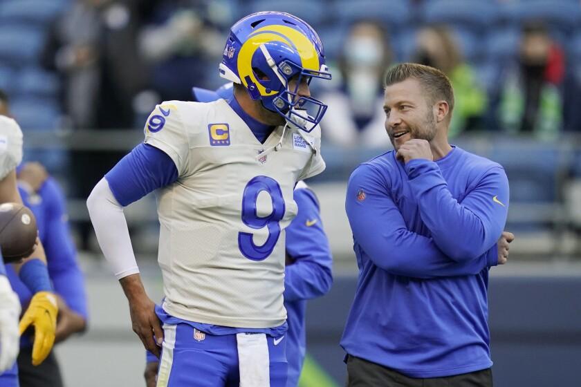 Los Angeles Rams quarterback Matthew Stafford (9) talks with head coach Sean McVay before an NFL football game against the Seattle Seahawks, Thursday, Oct. 7, 2021, in Seattle. (AP Photo/Elaine Thompson)