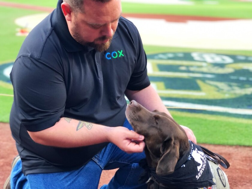 Army veteran Jon Marroquin, 33, takes comfort from his service dog, Berkeley, before throwing out the honorary first pitch Saturday at Petco Park in downtown San Diego.