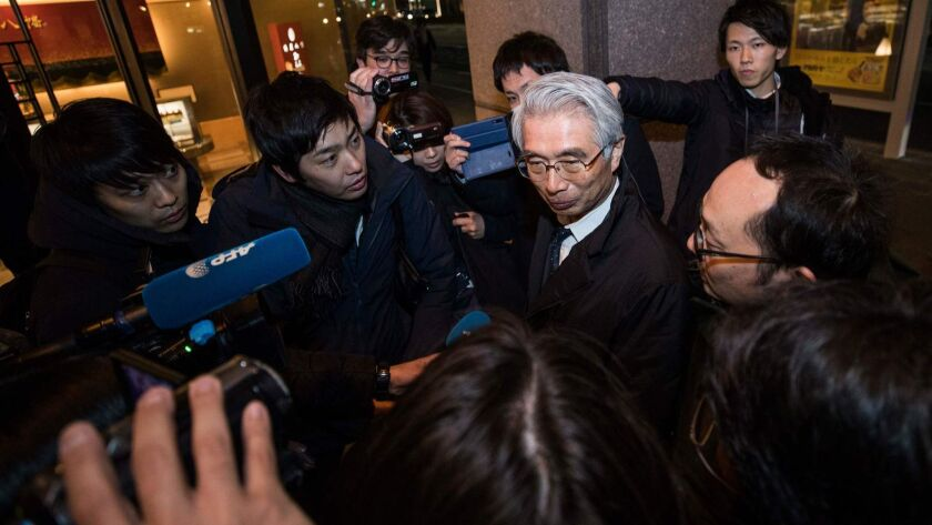 Junichiro Hironaka, center, the new lawyer of former Nissan chief Carlos Ghosn, speaks with the media outside his office building in Tokyo.