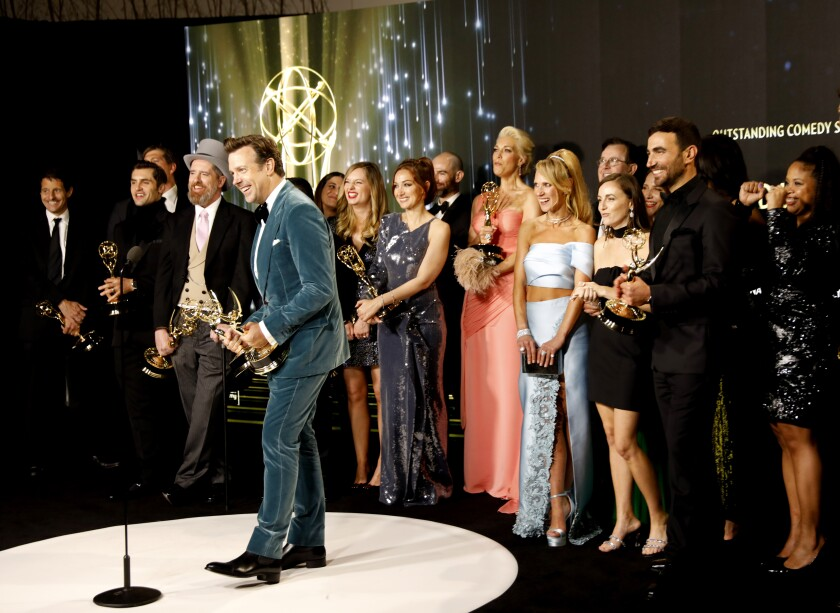 """Jason Sudeikis surrounded by the rest of the """"Ted Lasso"""" cast and crew with Emmy awards"""