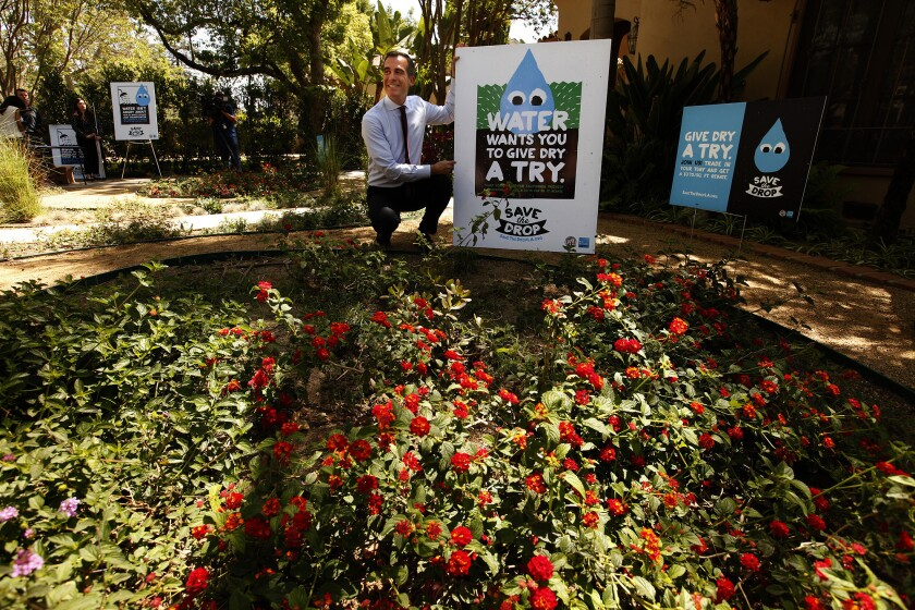 "Los Angeles Mayor Eric Garcetti poses with signage for his ""Save the Drop"" campaign after talking about the program to connect Angelenos with water conservation tools in Van Nuys on April 9."