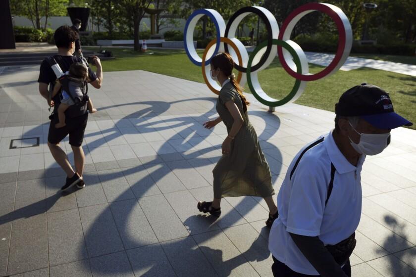 Transeúntes pasan frente a los anillos olímpicos en Tokio el 9 de junio del 2021. Hay una fuerte oposición a la realización de los Juegos Olímpicos, pero demasiados intereses en juego, que hacen que los organizadores insistan en realizar la justa en medio de una pandemia. (AP Photo/Eugene Hoshiko, File)