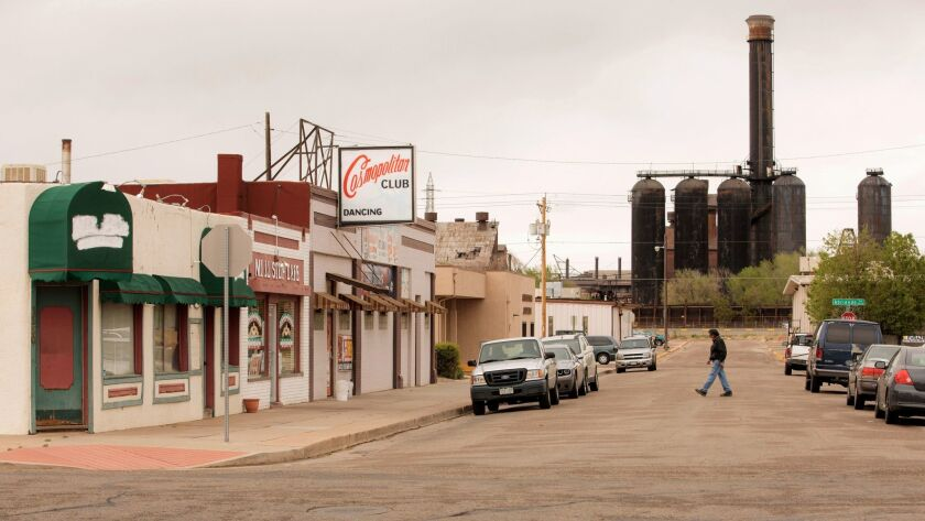 A man walks across the street in a portion of town with a view of a bit of the Steel Mill complex in