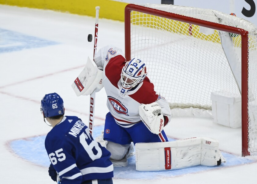 Montreal Canadiens goaltender Jake Allen (34) makes a save as Toronto Maple Leafs forward Ilya Mikheyev (65) looks for the rebound during the second period of an NHL hockey game Saturday, May 8, 2021, in Toronto. (Nathan Denette/The Canadian Press via AP)