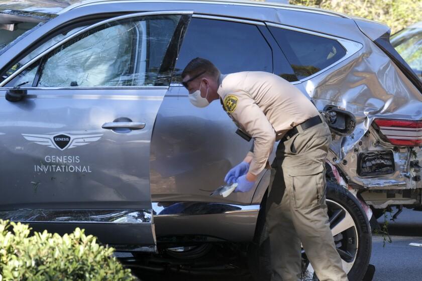 A deputy inspects a damaged vehicle.