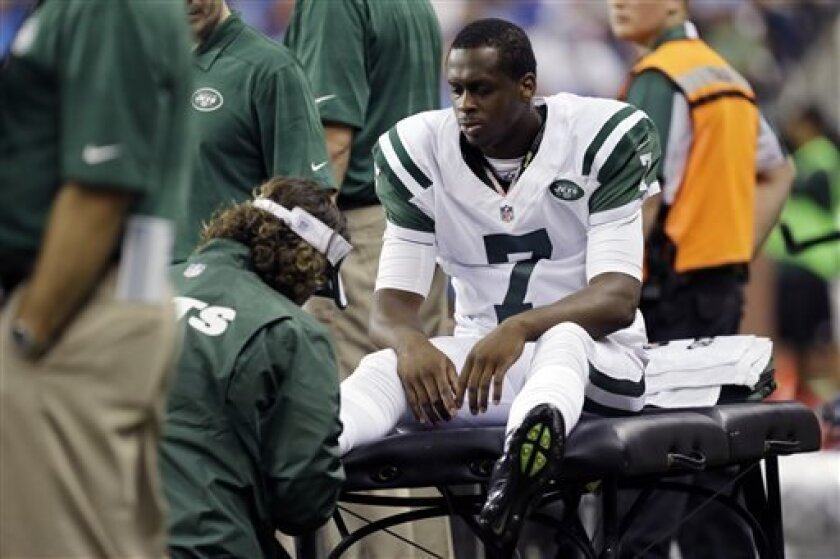 New York Jets quarterback Geno Smith (7) is examined during the third quarter of an NFL football game against the Detroit Lions at Ford Field in Detroit, Friday, Aug. 9, 2013. (AP Photo/Paul Sancya)