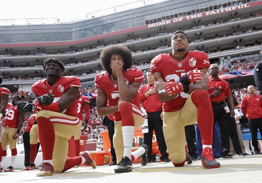 San Francisco 49ers' Eli Harold, left, Colin Kaepernick and Eric Reid kneel during the national anthem