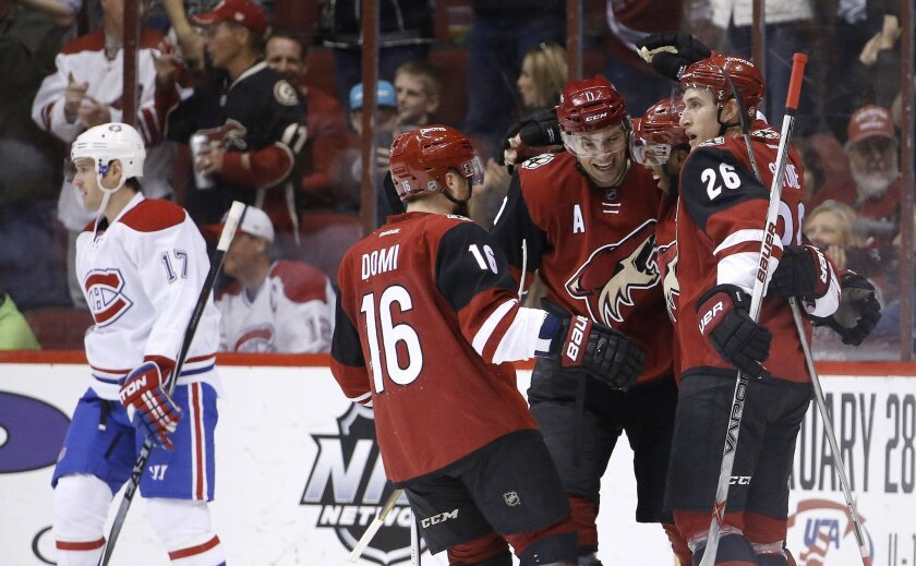 Arizona Coyotes' Anthony Duclair, second from right, celebrates his goal against the Montreal Canadiens with Michael Stone (26), Max Domi (16), and Martin Hanzal (11), of the Czech Republic, as Canadiens' Torrey Mitchell (17) skates away during the first period of an NHL hockey game Monday, Feb. 15