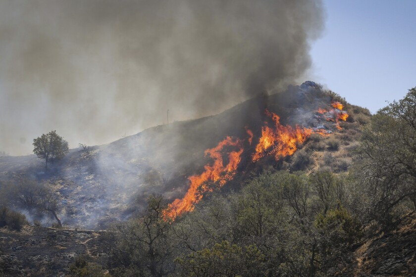 Flames erupt on a hillside along Mineral Spring Road west of Coalinga, Calif., at the Mineral Fire on Thursday, July 16, 2020. Firefighters aided by helicopters and air tankers battled a 26 square mile (66.7 square kilometers) wildfire in a rural area of Central California that is 20% contained, a fire command statement said. (Craig Kohlruss/The Fresno Bee via AP)