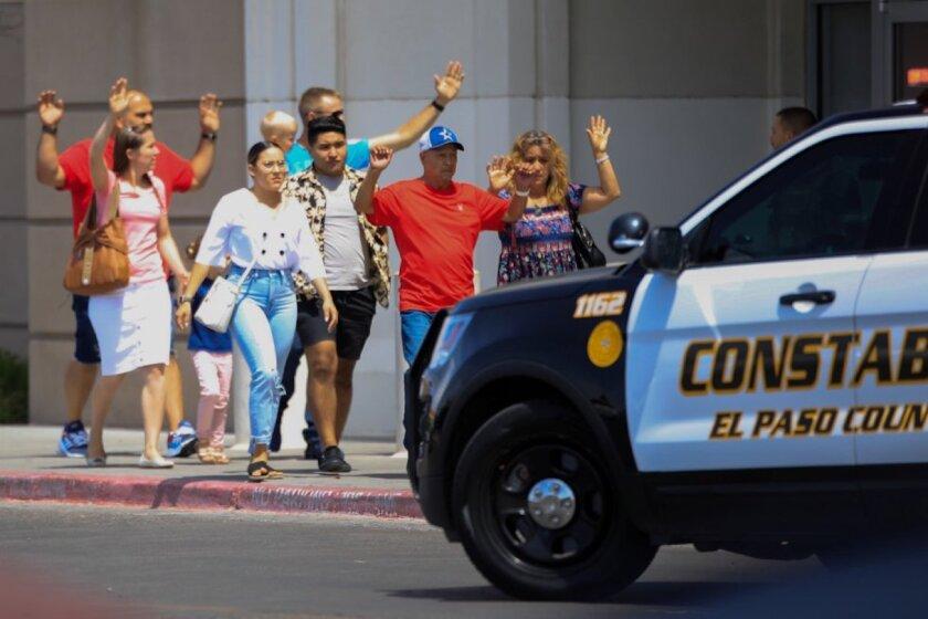 Varios clientes del centro comercial donde se registró el tiroteo en El Paso, Texas, salen del edificio con las manos en alto.