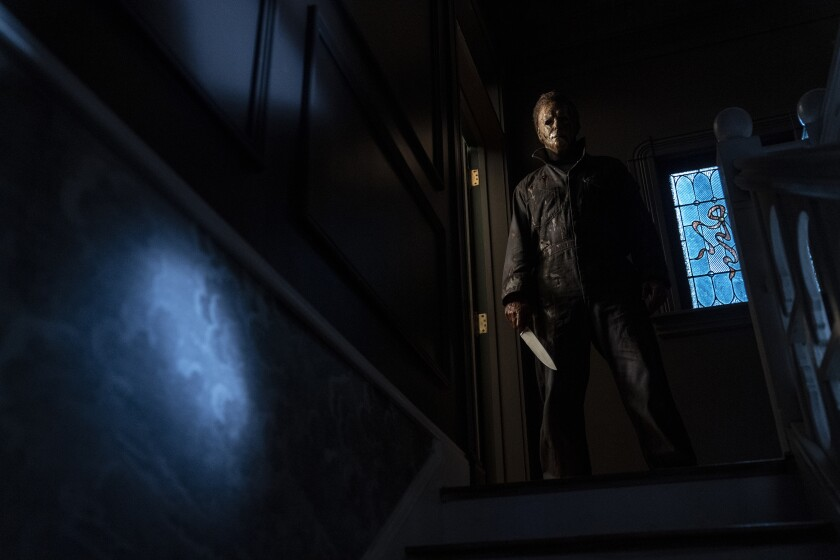 A masked figure holding a knife on a dark stairway