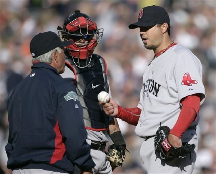 Boston Red Sox starter Josh Beckett, right, gives up the baseball to manager Bobby Valentine, left, as catcher Jarrod Saltalamacchia looks on in the fifth inning of a baseball game Saturday, April 7, 2012, in Detroit. Beckett was relieved after giving up back-to-back home runs to Detroit's Miguel Cabrera and Prince Fielder. (AP Photo/Duane Burleson)
