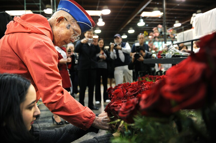 World War II veteran Robert Baba, 97, places a rose on a float sponsored by the city of Alhambra.