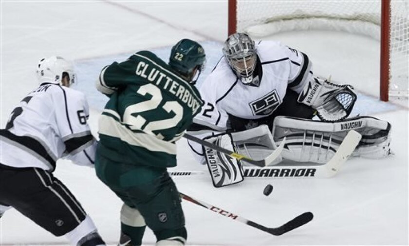 Los Angeles Kings goalie Jonathan Quick, right, deflects a shot by Minnesota Wild right wing Cal Clutterbuck (22) as Kings defenseman Jake Muzzin, left, defends during the second period of an NHL hockey game in St. Paul, Minn., Saturday, March 30, 2013. (AP Photo/Ann Heisenfelt)
