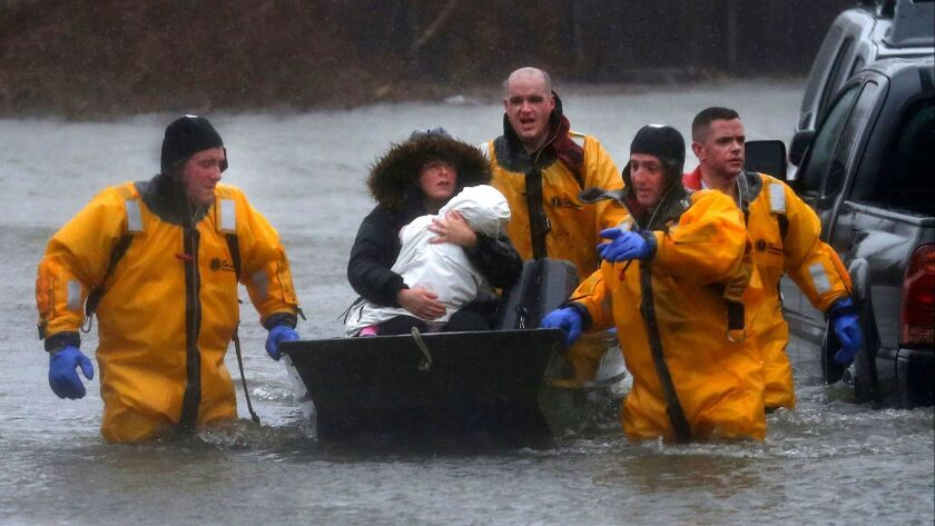 Quincy firefighters rescue a mother and child by boat after their residence was flooded along Post I