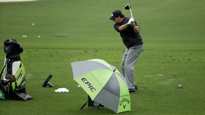 Phil Mickelson hits at the driving range during practice for the Masters golf tournament Tuesday, Ap