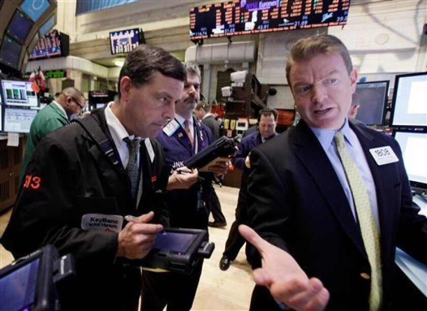 In this Feb. 8, 2012 photo, specialist Michael O'Mara, right, works on the floor of the New York Stock Exchange. Stock markets fell Friday, Feb. 10, 2012, after Greece's crucial international bailout was put on hold by its partners in the 17-nation eurozone, a day after it seemed that the country's tortuous journey to pacifying its creditors had reached a conclusion. (AP Photo/Richard Drew)
