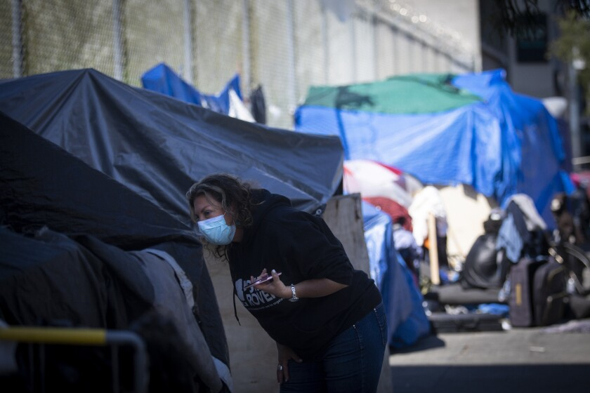 """Dr. Susan Partovi searches an encampment for people who may be experiencing symptoms of the coronavirus. """"Is anyone around here sick?"""" she asked."""