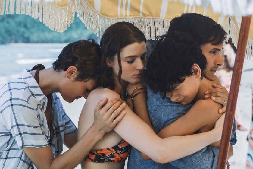 A group of emotional people embrace beneath a beach umbrella.
