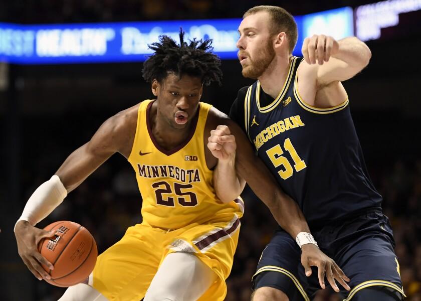 Michigan's Austin Davis (51) guards against Minnesota's Daniel Oturu (25) in the first half during an NCAA college basketball game on Sunday, Jan. 12, 2020, in Minneapolis. (AP Photo/Hannah Foslien)