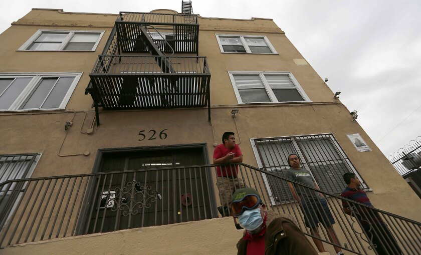 Men stand outside an apartment building in the Westlake District of Los Angeles, which has the second-highest population density in the city, with about 38,214 people per square mile.