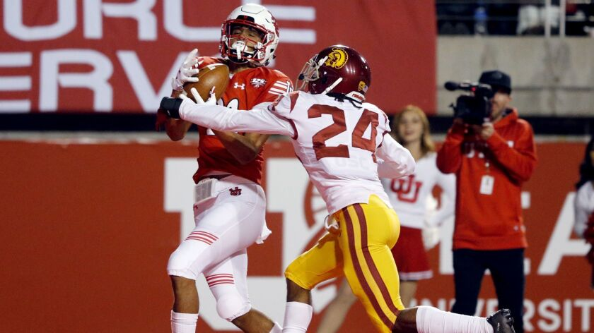 Utah wide receiver Solomon Enis, left, catches a touchdown as USC cornerback Isaiah Langley (24) defends during the second half on Saturday in Salt Lake City.