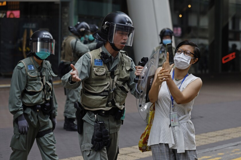 A riot officer pushes a woman photographing detained protesters in Hong Kong's Mong Kok district on May 27, 2020.